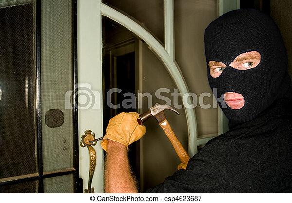Aburglar robbing a house wearing a balaclava. - csp4623687