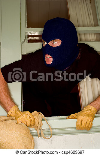 Aburglar robbing a house wearing a balaclava. - csp4623697