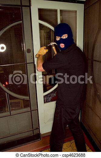 Aburglar robbing a house wearing a balaclava. - csp4623688