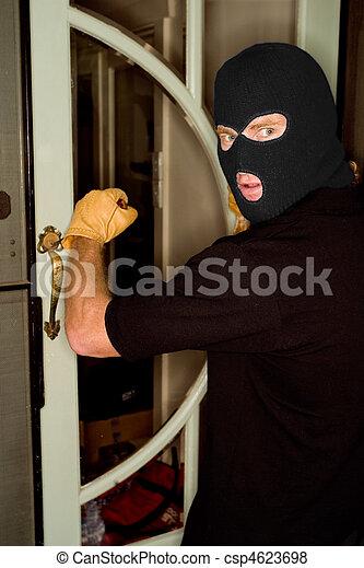 Aburglar robbing a house wearing a balaclava. - csp4623698