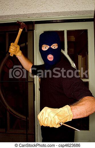 Aburglar robbing a house wearing a balaclava. - csp4623686