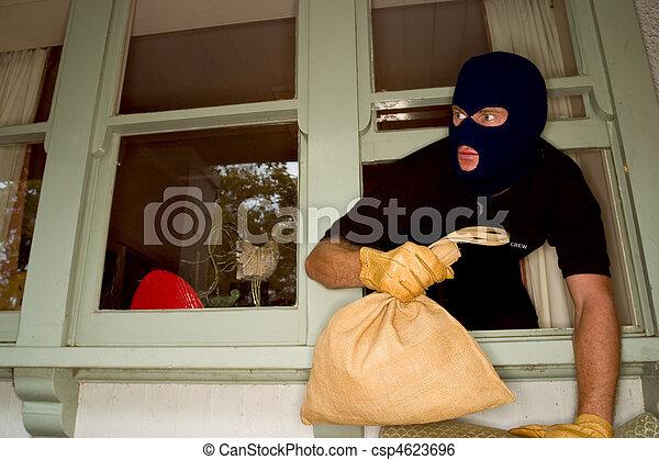 Aburglar robbing a house wearing a balaclava. - csp4623696