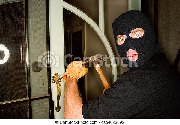 Aburglar robbing a house wearing a balaclava. - csp4623692