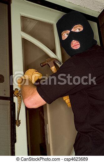 Aburglar robbing a house wearing a balaclava. - csp4623689