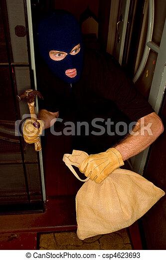 Aburglar robbing a house wearing a balaclava. - csp4623693