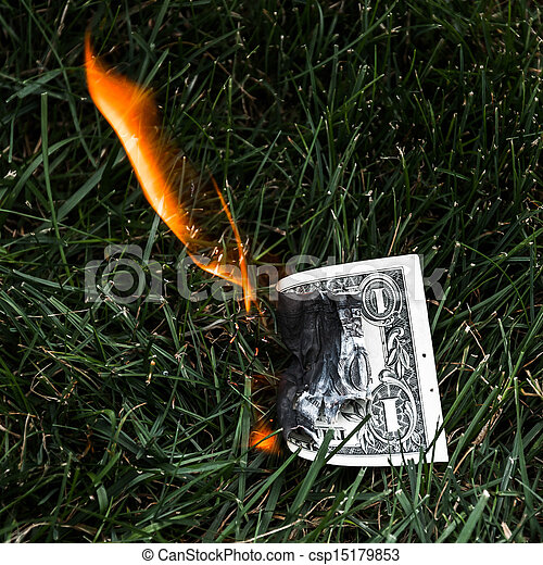 A burning dollar bill in the grass. - csp15179853