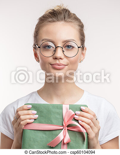 a charming young woman with Christmas gift looking at the camera - csp60104094