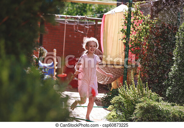 A cheerful charming seven-year-old girl enjoys a sunny summer morning and has fun in the garden at home - csp60873225