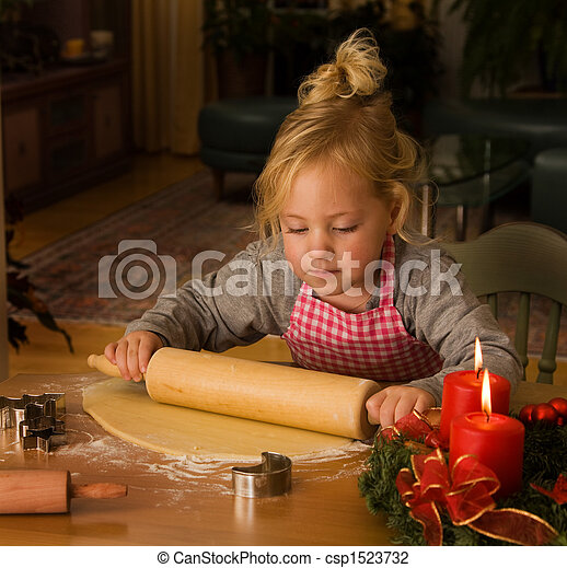 A child at Christmas in Advent when baking cookies - csp1523732
