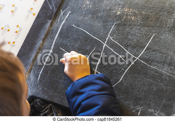 A child's hand drawing on a blackboard with chalk - csp81845261