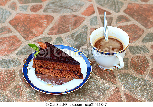 A chocolate cake with a cup of coffee. - csp21181347