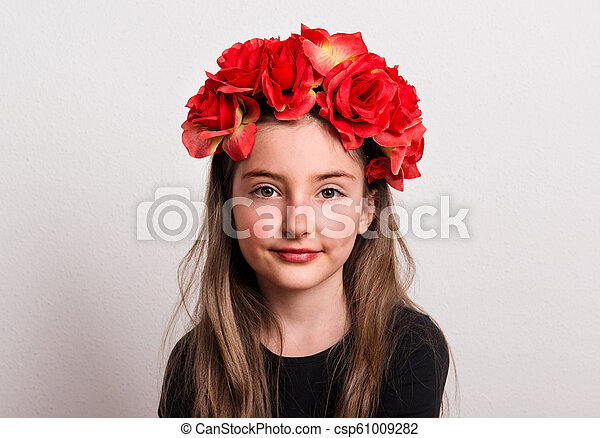 A close-up of small girl with flower headband sitting in a studio. - csp61009282