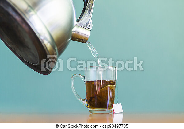 A close up water pouring into glass cup tea - csp90497735