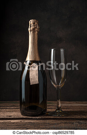 A closed bottle of champagne and an empty wine glass on a wooden background. - csp86529785