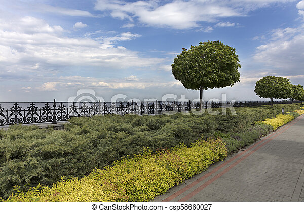 A cobbled stepped path along the embankment of the river, framed by a metal decorative fence cut off by bushes and trees in a beautiful park - csp58660027