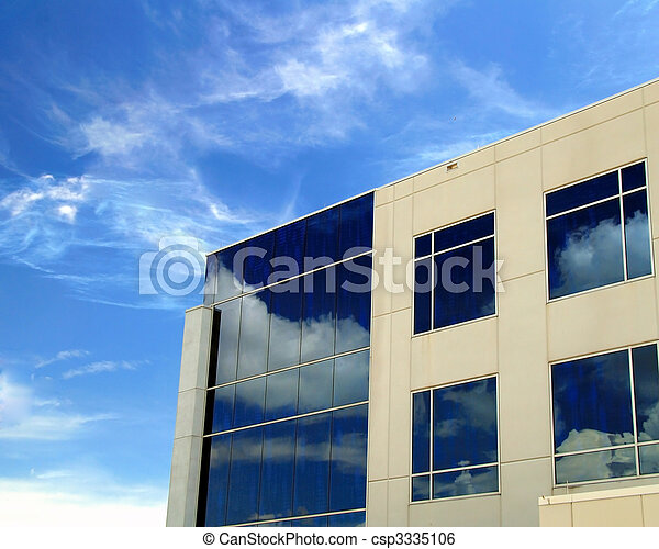 A commercial building with reflective mirror windows and beautiful blue sky background - csp3335106