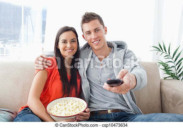 A couple embracing while on the couch changing the channel - csp10473634