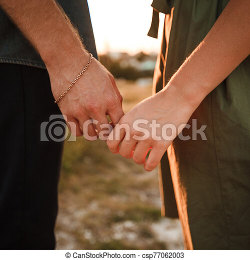 A couple holds hands. Delicate gesture of love on Valentine's Day - csp77062003