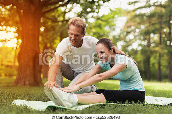 A couple is engaged in sports in a warm summer park. A man helps a woman stretch. - csp52526493