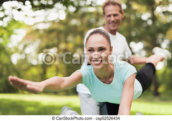 A couple is engaged in sports in a warm summer park. A man helps a woman stretch. - csp52526434