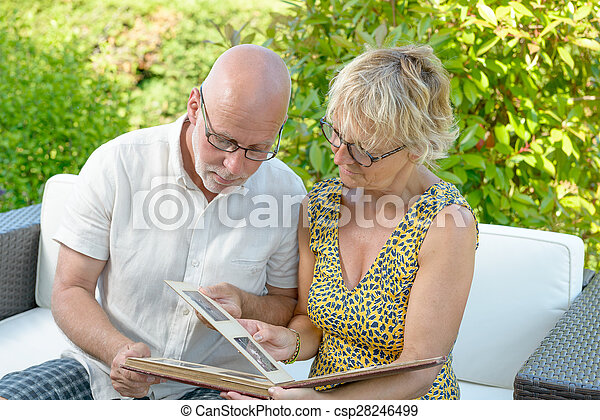 a couple looking at a photo album - csp28246499