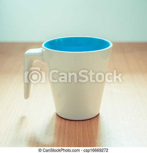 A cup of coffee on wooden background - csp16669272