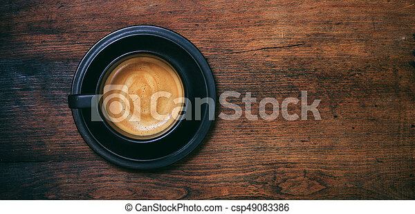 A cup of coffee on wooden background - csp49083386
