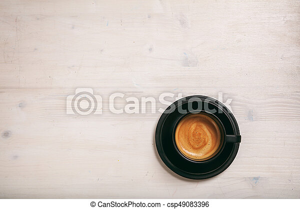 A cup of coffee on wooden background - csp49083396