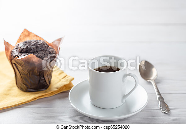 A cup of coffee with chocolate muffin on wooden table - csp65254020