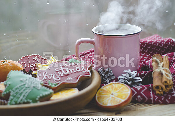 A cup of hot tea stands on a wooden table next to a wooden plate on which are gingerbread cookies made from orange slices against the background of a window with water drops - csp64782788