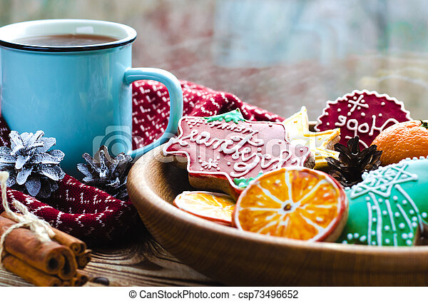 A cup of hot tea stands on a wooden table next to a wooden plate on which are gingerbread cookies made from orange slices against the background of a window with water drops - csp73496652