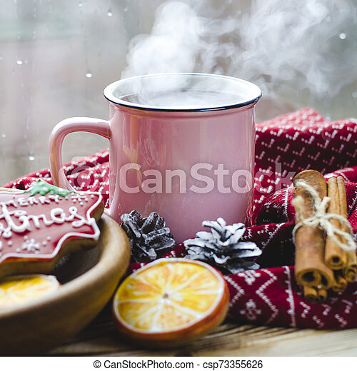 A cup of hot tea stands on a wooden table next to a wooden plate on which are gingerbread cookies made from orange slices against the background of a window with water drops - csp73355626