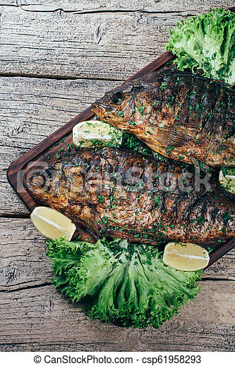 A deliciously roasted carp on a grill, presented on a wooden board, and along the leaves of green salad and pieces of lemon - csp61958293