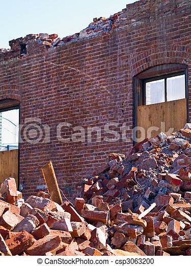A demolition site with a pile of demolished brick wall and concrete debris - csp3063200