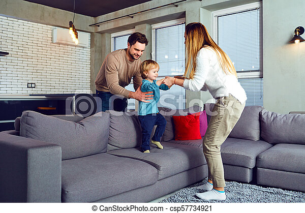 A family is playing with a child in the room. - csp57734921