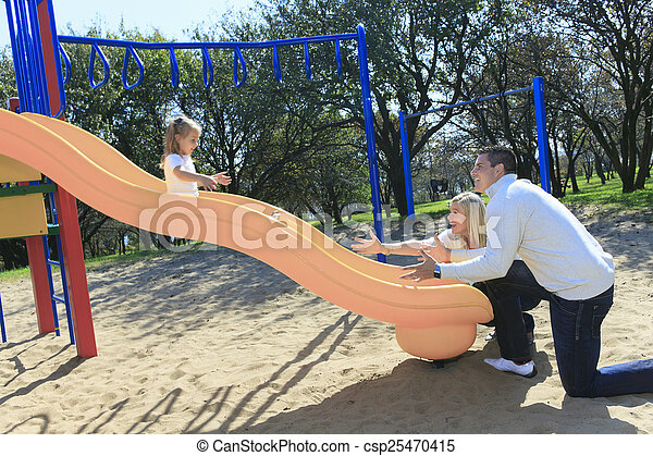 A Father and daughter playing on a slide - csp25470415