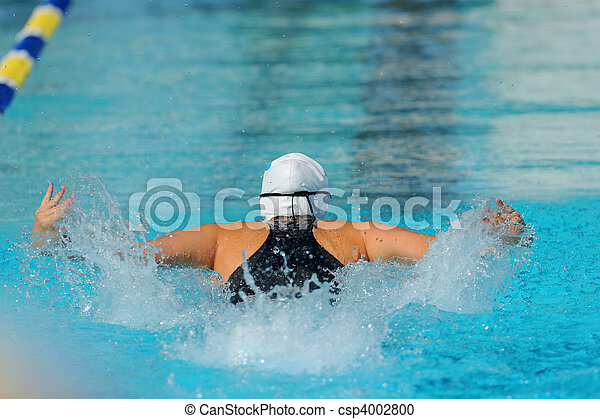A female butterfly swimmer in action during a race. - csp4002800