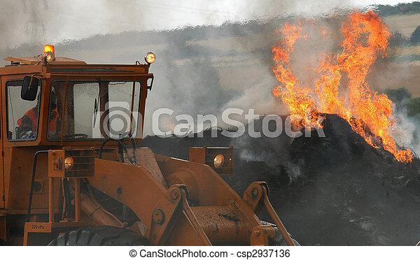A fireman estinguishing fire of tyres - csp2937136