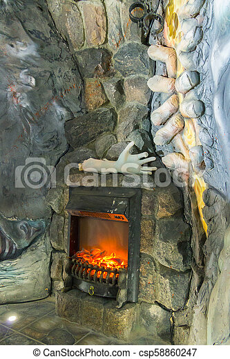 A fireplace made in the wall made of stone. With an unusual setting, the model of a hand lying on it and an unusual stucco on the wall next to it. - csp58860247