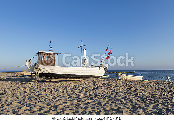 A fishing boat on shore of the Baltic Sea in Koserow, Germany. - csp43157616