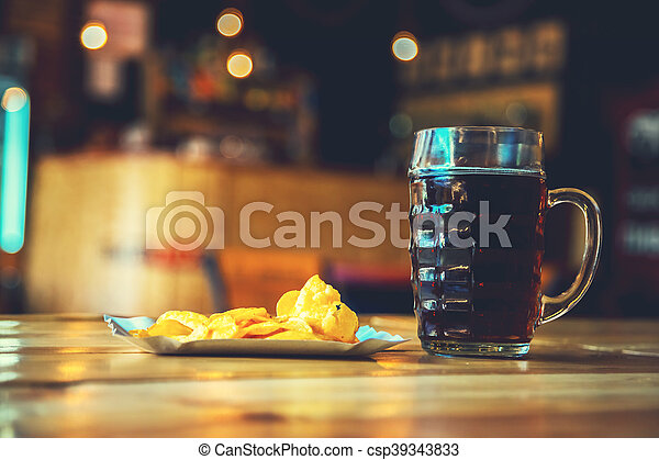A fresh glass of cold dark beer and potato chips on the wooden bar counter in pub with free space for your text. Beautiful background of the Oktoberfest. - csp39343833