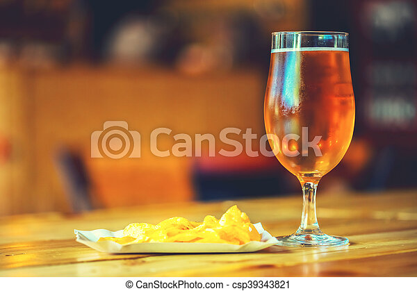A fresh glass of cold light beer and potato chips on the wooden bar counter in pub with free space for your text. Beautiful background of the Oktoberfest. - csp39343821