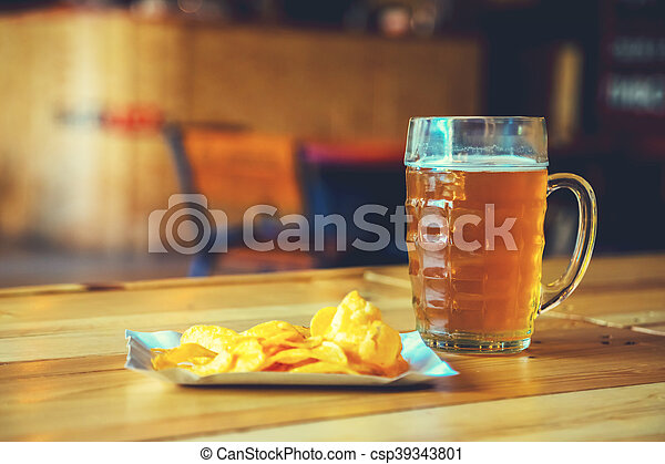 A fresh glass of cold light beer and potato chips on the wooden bar counter in pub with free space for your text. Beautiful background of the Oktoberfest. - csp39343801