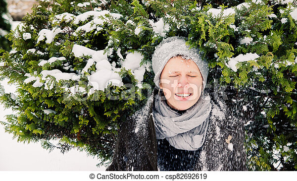 a girl laughing under the snow falling from a fur tree - csp82692619