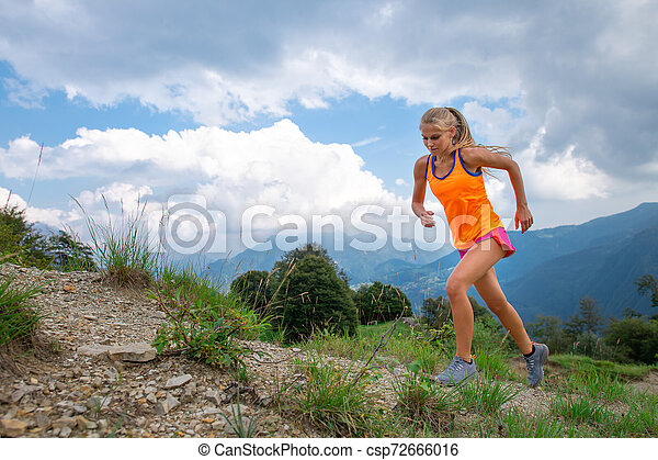 A girl practice running on trail in the mountains - csp72666016