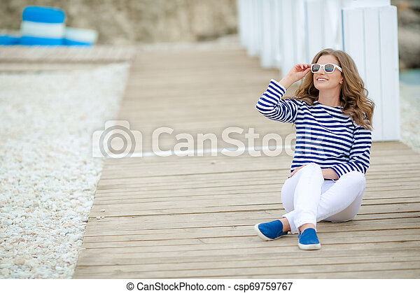 A Glamorous pretty young hipster woman in summer white t-shirt in sneakers in trendy jeans in stylish sunglasses is standing near a wooden wall in the city. European girl on a walk on a sunny summer day - csp69759767