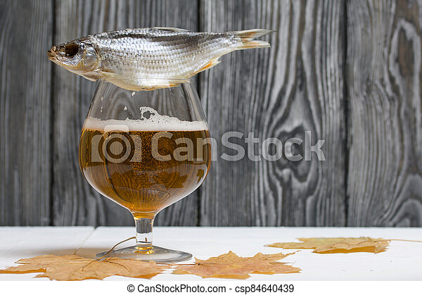 A glass of beer and dried maple leaves. There is a roach on the glass. - csp84640439
