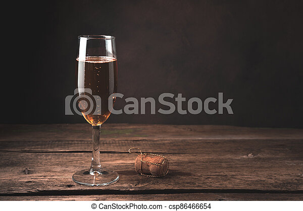 A glass of champagne and a bottle stopper on a wood background. - csp86466654