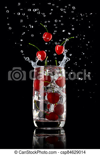 A glass of cherry lemonade with ice, splashing in different directions and three cherry berries falling into the glass, on a black background - csp84629014