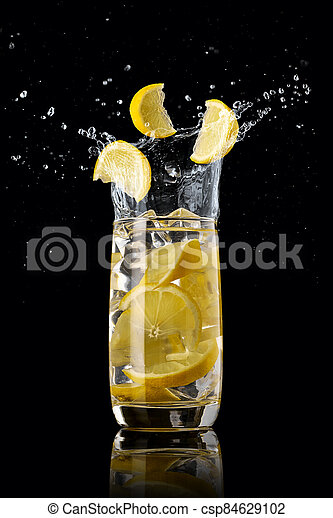 A glass of lemon lemonade with ice, splashing in different directions and three slices of lemon falling into the glass, on a black background - csp84629102